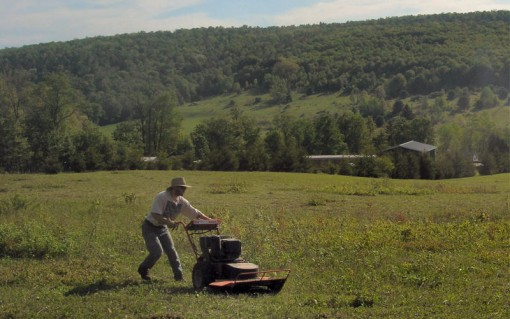 image of a man operating a walk behind field mower - photo taken by Cadie on May 28, 2006