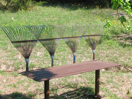 Image of bench with old leaf rakes for the back of the bench