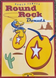 Image of Round Rock donut box. One donut has horns like a longhorn cow; a cowboy is riding the other donut and attempting to lasso the longhorn donut.
