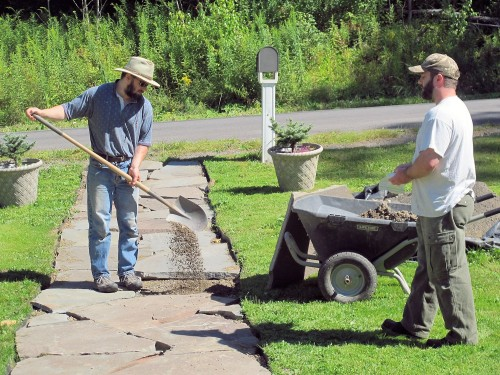 Crushed bluestone is used to make a level base for the large bluestone paver.