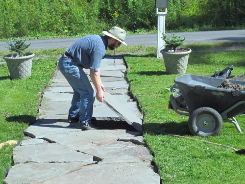 Carefully replace the stone in the walk after the base has been leveled.