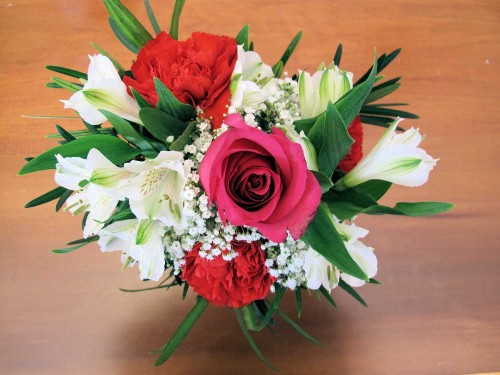 Flower arrangement of red carnations, white alstroemeria, baby's breath, and one red rose.