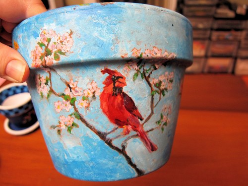Clay pot painted with a cardinal and apple blossoms.