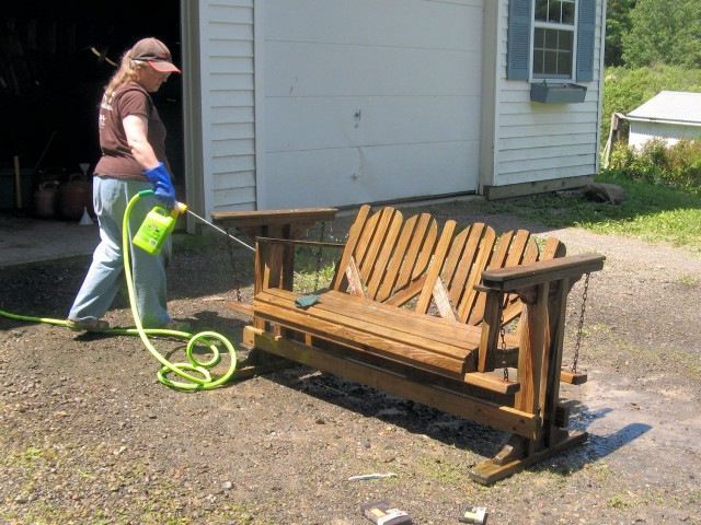 Spraying deck cleaner to restore wooden outdoor furniture